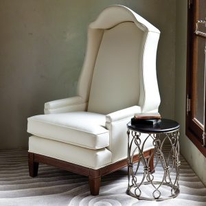 Sitting area featuring high end home furnishings including a white high back chair with an end table